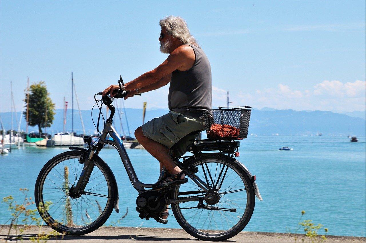 Homme âgé entrain de faire di vélo électrique en bord de plage