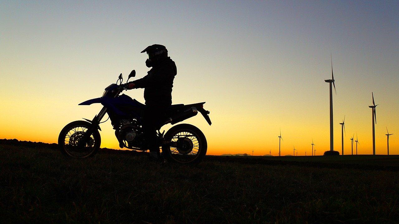 Homme sur une moto roulant lors d'un coucher de soleil