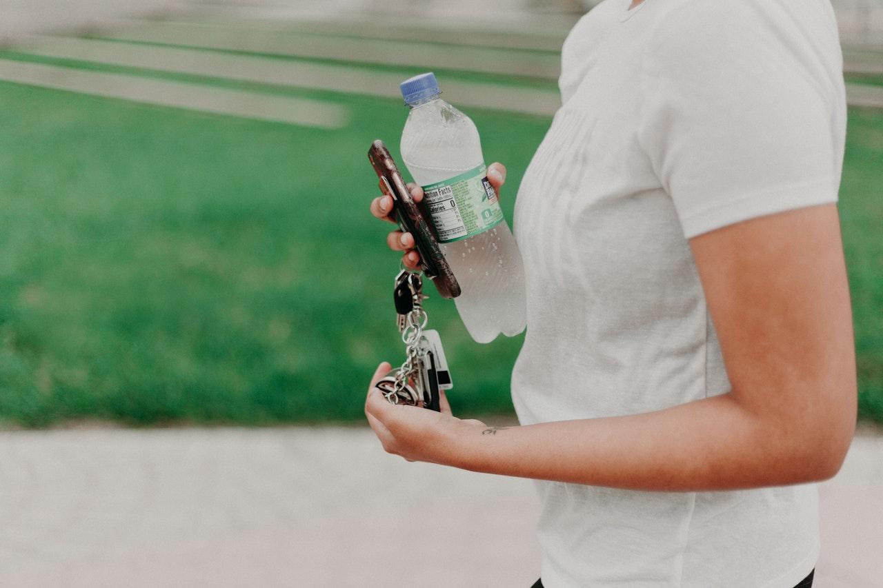 Homme portant un t-shirt blanc et tenant ses clés et une bouteille à la main