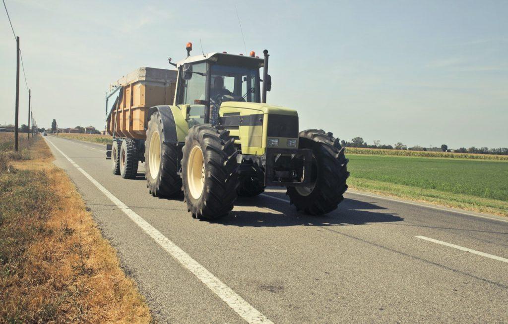 Véhicule agricole, tracteur, roulant sur la route entre les champs