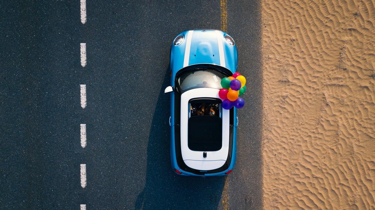 Voiture de la marque Mini vue du ciel avec toit ouvrant et ballons de baudruche colorés