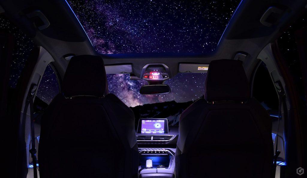 Intérieur d'une Peugeot 3008 avec toit panoramique vue du ciel étoilé
